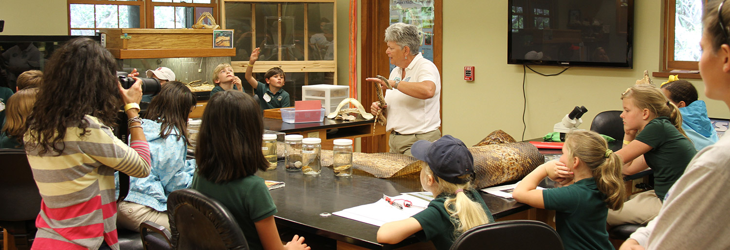 classroom of kids and instructor observing snakes